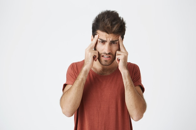 Shot of stylish bearded caucasian man holding fingers on his temples with suffering expression, as if trying to remember something important or having headache