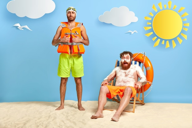 Shot of surprised red head guy with suncream on sunburned skin, rests on beach chair, looks with shock at camera, friend stands near, wears protective lifejacket, goggles. two companions on beach