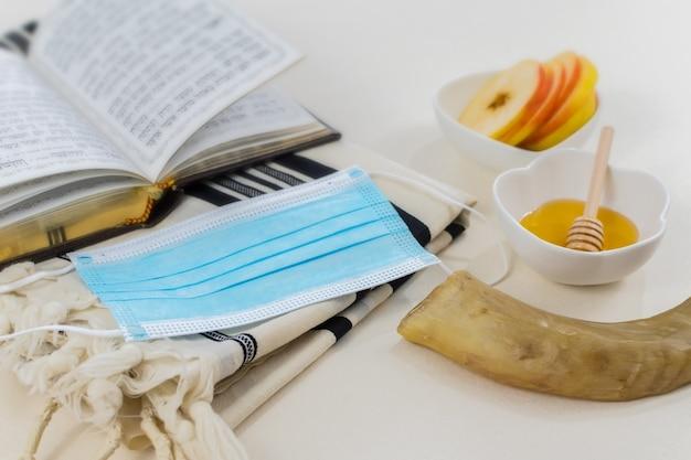 Colpo di simboli del nuovo anno ebraico e una mascherina medica su bianco