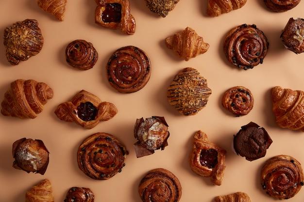 Sopra scatto di gustosi stuzzicanti dolciumi per soddisfare i vostri golosi. pasticceria con ripieni e focacce all'uvetta, muffin al cioccolato, croissant su fondo beige. prodotti da forno freschi ad alto contenuto calorico