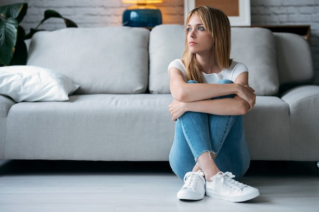 Shot of thoughtful young woman looking to the side while sitting on the floor in the living room at home.