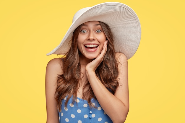 Shot of thrilled smiling young lady has natural dark hair, white teeth, broad smile, touches cheek with hand, wears stylish summer hat, feels amazed by great news, isolated over yellow wall