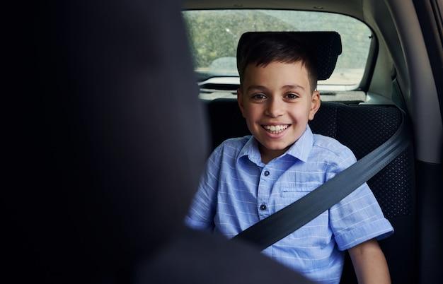 Снято через сиденье водителя улыбающегося школьника, пристегнутого ремнем безопасности, во время поездки на автомобиле в безопасном детском автокресле