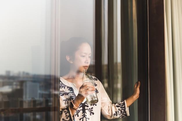 Shot through window woman relaxing holding botttle of water.
