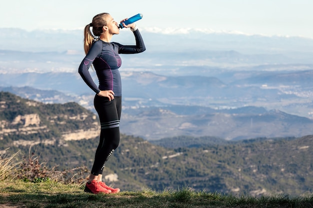 Shot of trail runner drinking water while looking landscape from mountain peak.