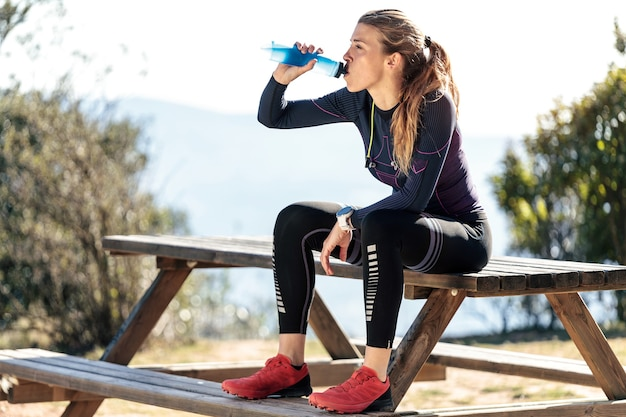 Shot of trail runner drinking water while sitting on bench for relaxing one moment on mountain peak.