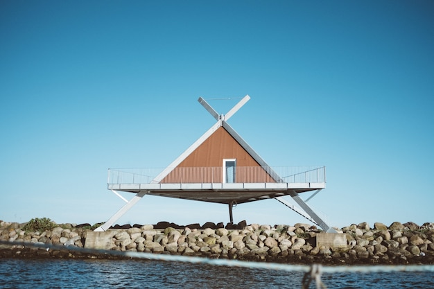 Shot of a triangle-shaped house in front of water under a blue sky