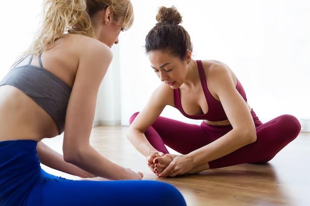 Shot of two pretty young sporty women practicing yoga at home. baddha konasana pose.