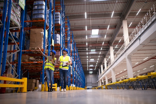 Shot of two workers walking through large warehouse center, observing racks with goods and planing distribution to the market