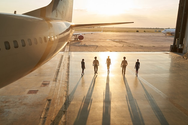 Shot of unidentifiable pilots and stewardesses walking out of a hangar at sunset