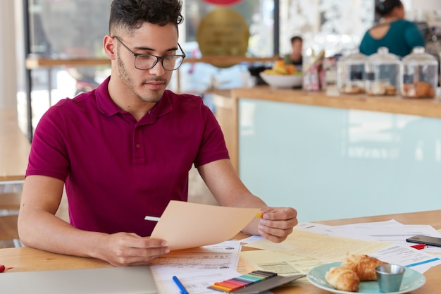 Shot of unshaven guy examines paperwork, uses stickers, dressed in casual t shirt and spectacles. creative male blogger works with documentation, has hard working day, develops new strategy.
