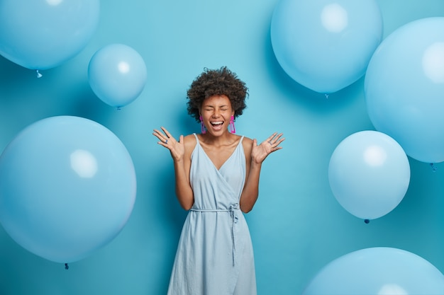 Shot of upbeat cheerful dark skinned woman feels very happy and excited, raises palms and laughs, spends free time on party, wears nice blue summer dress with earrings and rings, poses near balloons