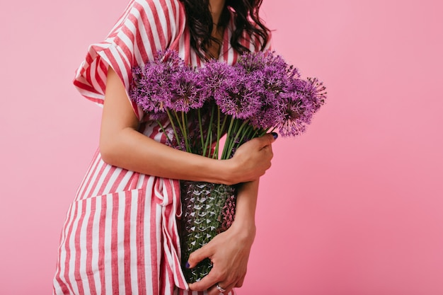 Shot of violet wild flowers in vase closeup. girl in pink sundress holds bouquet.