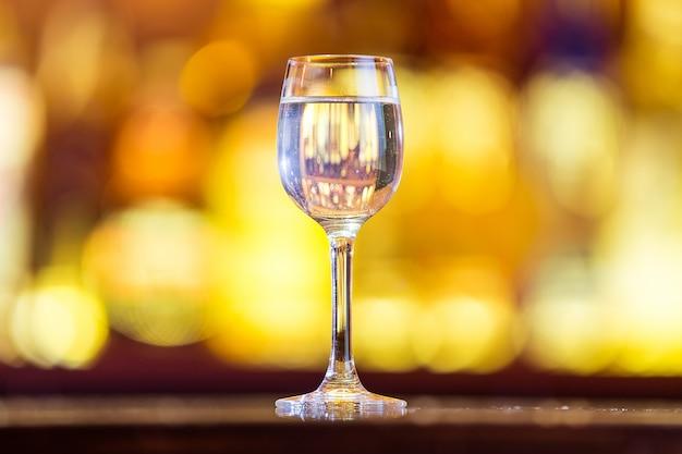 Shot of vodka on the bar on bright lights.