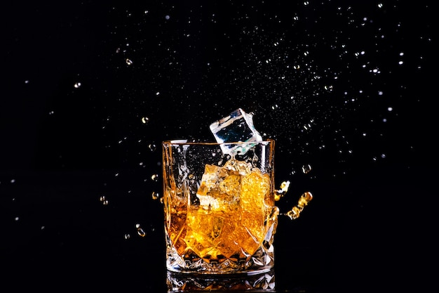 Shot of whiskey with splash on black surface, brandy in a glass