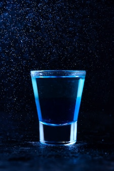 Shot with white rum and liquor blue curacao. alcoholic layer cocktail in freeze motion, drops in liquid splash on dark wall