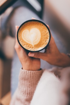 Shot of woman hands hold cup of hot coffee with heart design made of foam.