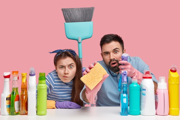 Shot of woman and man look scrupulously, do housework, clean everything, hold sponge and broom, sit at workplace with detergents, isolated over pink wall. household duties