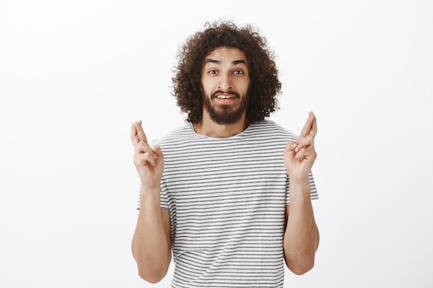 Shot of worried handsome bearded eastern male model with afro hairstyle in striped t-shirt, raising crossed fingers and hoping, making wish and begging faith to fulfill it
