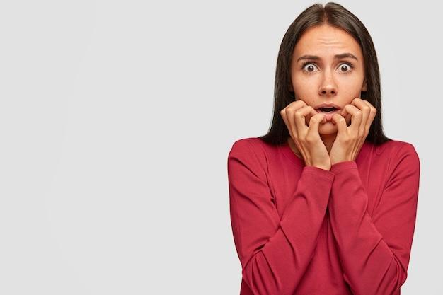 Shot of worried scared brunette young lady bites finger nails nervously