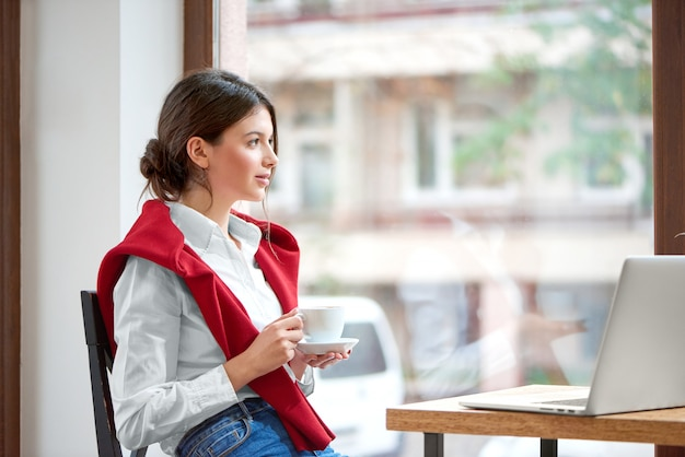 Shot of a young attractive woman having coffee at the cafe sitting relaxed looking at the window copyspace laptop computer technology connectivity mobility wireless project morning businesswoman.