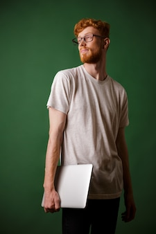 Shot of young bearded readhead hipster, holding laptop, looking away