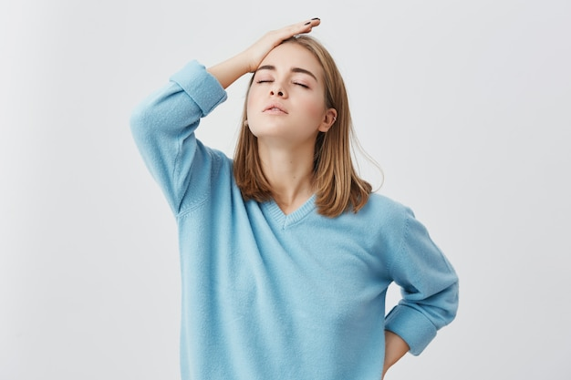 Shot of young beautiful student female with fair hair wearing blue sweater closing her eyes holding hand on her head being tired after hard work trying to relax. tired and annoyed.
