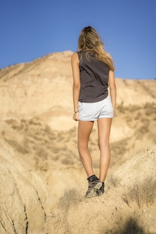 Behind shot of a young blonde girl in the desert in las bardenas reales, navarra. spain