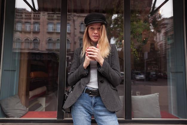 Colpo di giovane donna graziosa dai capelli lunghi bionda in abiti eleganti che camminano all'aperto nel fine settimana, bevendo una tazza di caffè in attesa di amici e guardando attentamente