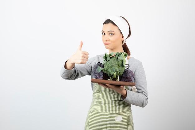 Colpo di giovane cuoco che tiene un piatto di cavoli e broccoli e dà i pollici in su