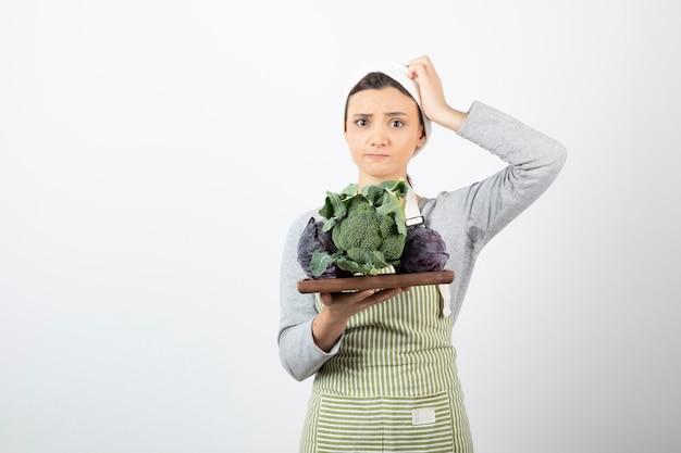 Colpo di giovane cuoco che tiene piatto di cavolo e broccoli su bianco