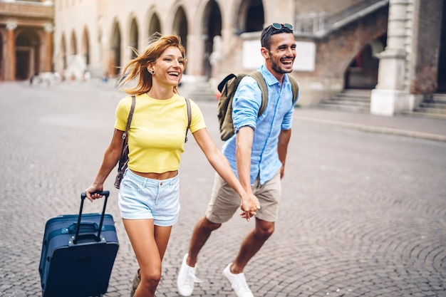 Shot of young couple holding hands and running in the city carrying suitcase at holiday.