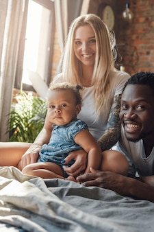 Shot of young family of joyful multiethnic couple and their daughter in bedroom.