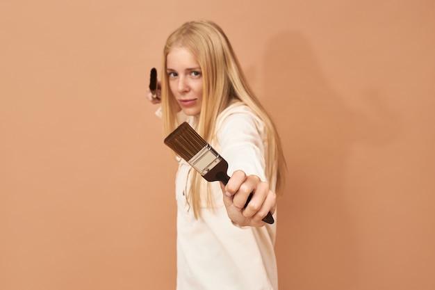 Colpo di giovane donna imbianchino in uniforme in posa isolato con due pennelli nelle sue mani