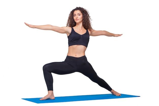 Tiro di una giovane donna in forma facendo esercizi di yoga.