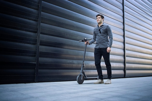 Colpo di giovane uomo bello in piedi dal suo scooter elettrico sulla strada