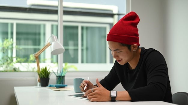 Shot of a young male graphic designer sketching on his project with digital tablet at modern workplace.