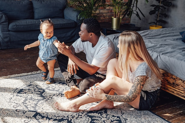 Shot of young mixed race family of caucasian mother and african father with their child.