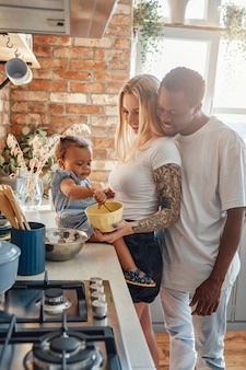 Shot of young mixed race family cooking food together on cozy kitchen in daytime.