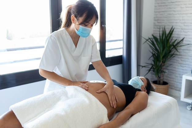 Shot of young physiotherapist woman massaging tummy on pregnant woman on a stretcher at home. women wearing surgical mask and new normal concept.