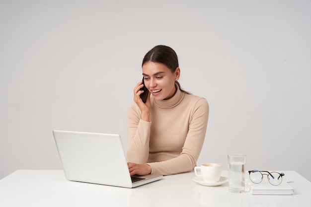 Shot of young pretty positive dark haired lady with natural makeup smiling cheerfully while making call and looking at screen while typing text on keyboard, isolated over white wall