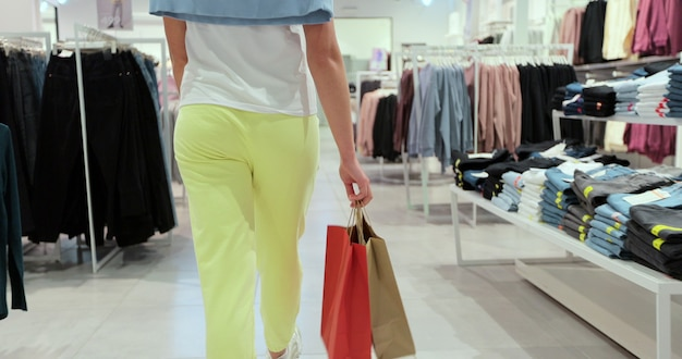 Shot of young woman leg walking with shopping bags though a clothing store.