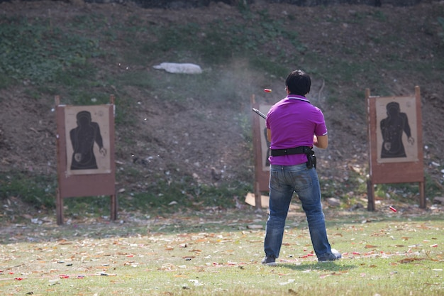 Shoter shooting  gun on an outdoor shooting range, selective focus