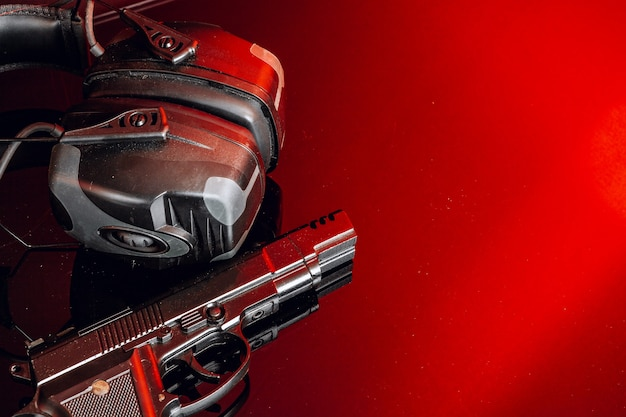 Shotgun and protective earphones on background with red light close up