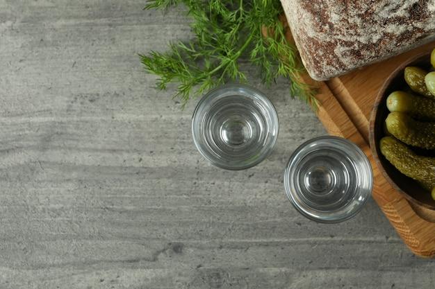 Выстрелы напитка, солений, хлеба и укропа на сером столе