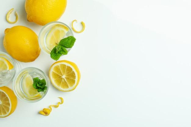 Выстрелы водки и лимонов на белом фоне