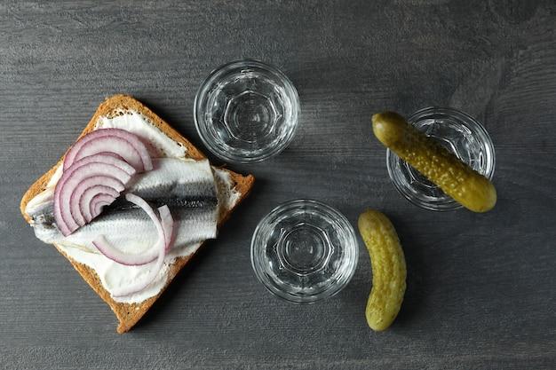 Рюмки водки и вкусные закуски на темном деревянном фоне