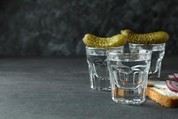 Рюмки водки и вкусные закуски на темном деревянном столе