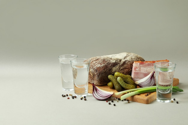 Рюмки водки и вкусные закуски на светло-сером фоне