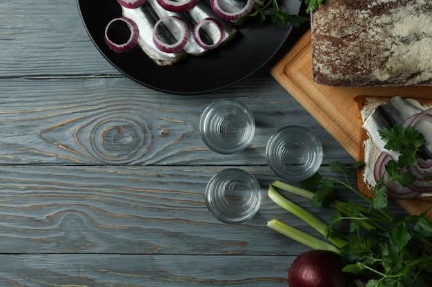 Рюмки водки и вкусные закуски на деревянном столе, место для текста